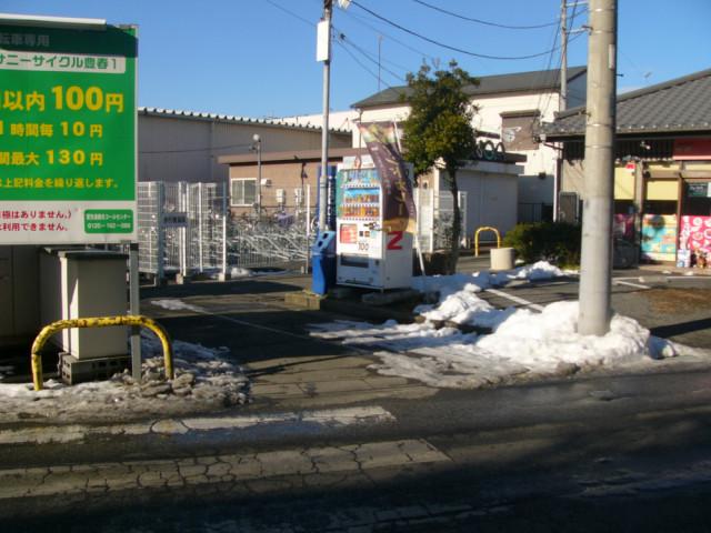 カレー屋さんの駐車場が右側で自転車置き場に向かう道の案内写真